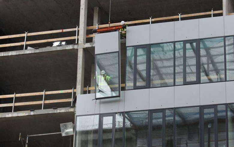 What is a unitized curtain wall and a half-unit curtain wall